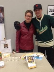 Woman and man in hockey jersey stand behind a table with brochures displayed