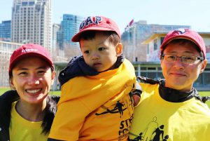 Woman and man holding young child smiling in yellow T-shirts and red ball caps