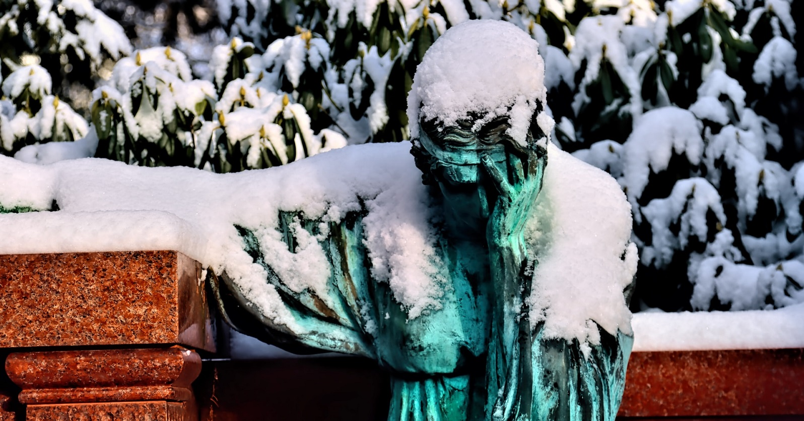 Statue of grieving figure covered with snow