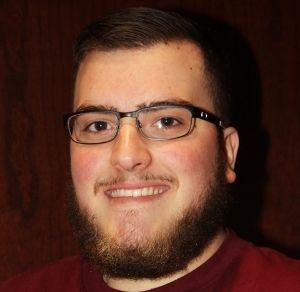 Headshot of Alex smiling, wearing glasses