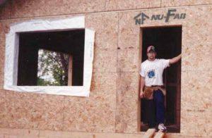man stands in open doorway of house mid-construction