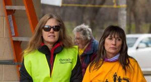 Two women stand outside. One is wearing sunglasses and a Threads of Life vest. The other is looking off into the distance.