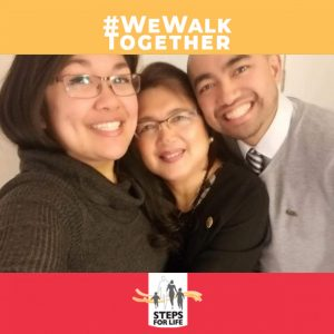 Two women and a man huddle and smile. Hashtag #WeWalkTogether placed at top and Steps for Life logo at bottom.