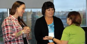 two women talking while woman smiles