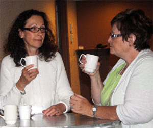 two women sit at table talking and holding coffee cups