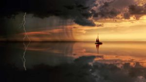 Silhouette of a sailboat on the horizon in a late evening sky with storm clouds roaring above