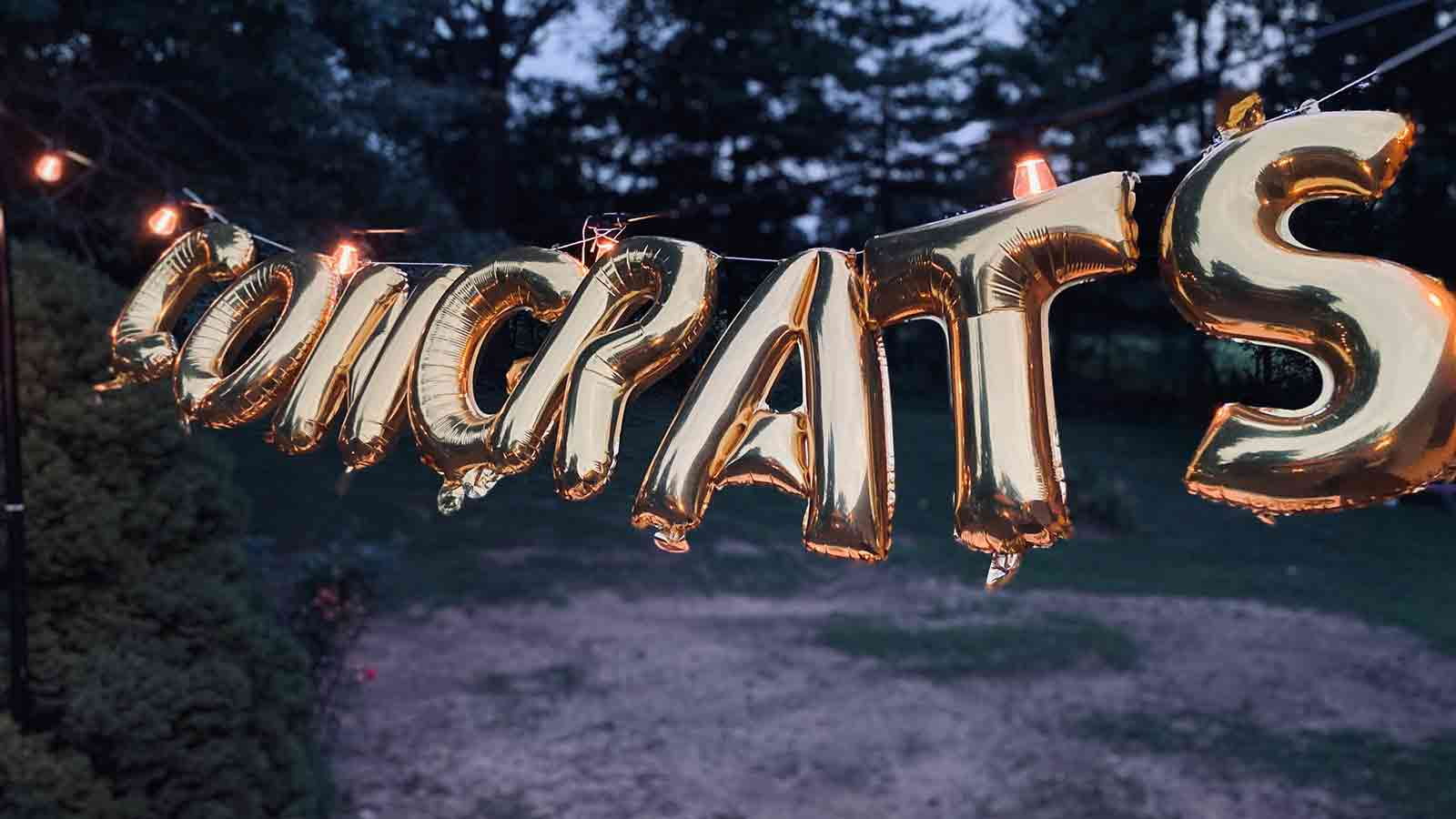 Gold balloon letters hanging that read Congrats