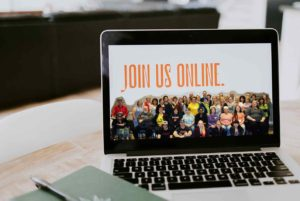 """Image of large group of people with text """"Join us online"""" above on laptop sitting on desk desk"""