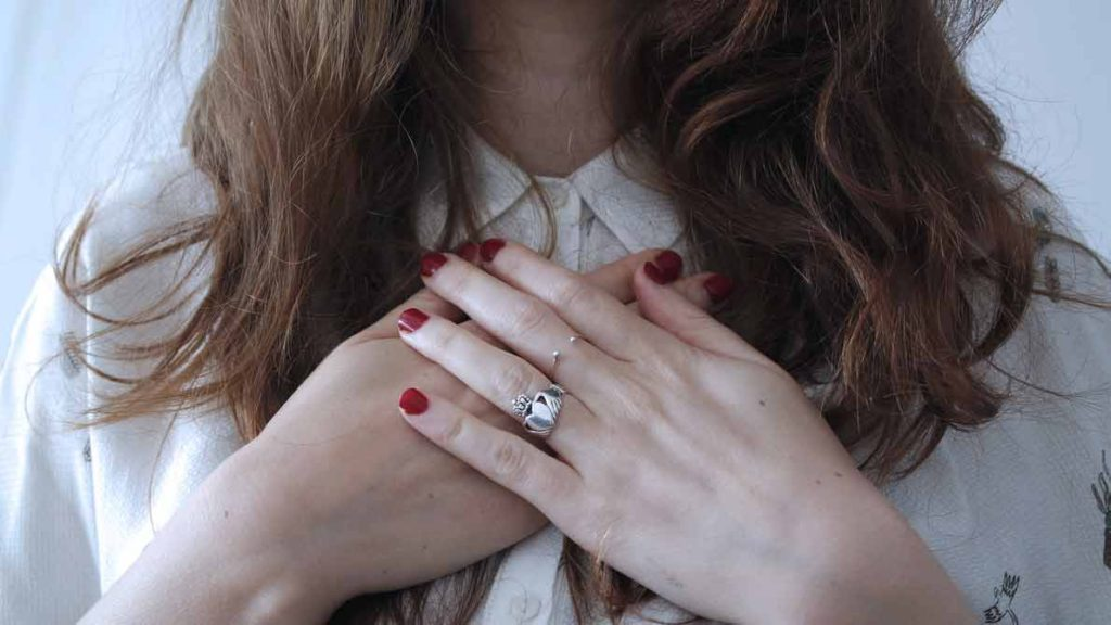 closely cropped image of woman's hands crossed over her chest