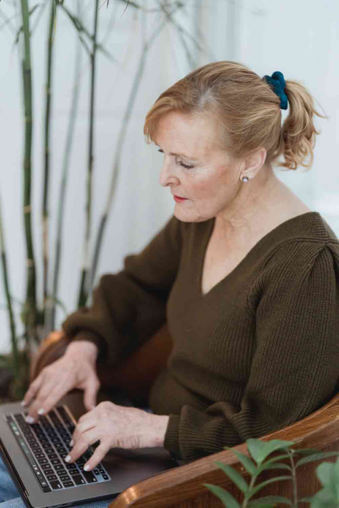 mature woman sits facing an open laptop. Her hands are positioned to type.