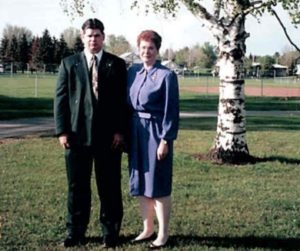 Young man and older woman stand in dress clothes in front of a tree