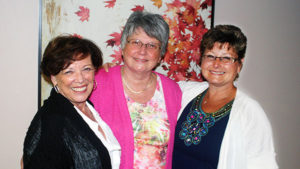 Three women gathered and smiling for the camera